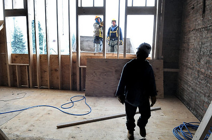 Scott Jones (left), of Cazenovia, and Tim Yousey work on the windows of the building at 401 First St. in Liverpool, which is being converted into office space and apartments.